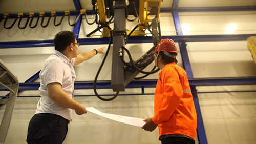 山東開泰研發人員在觀摩智能噴砂機器人工作運行